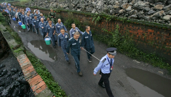 A policeman leads inmates as they walk along a road with their wrists tied together to a rope at Emei Mountain region