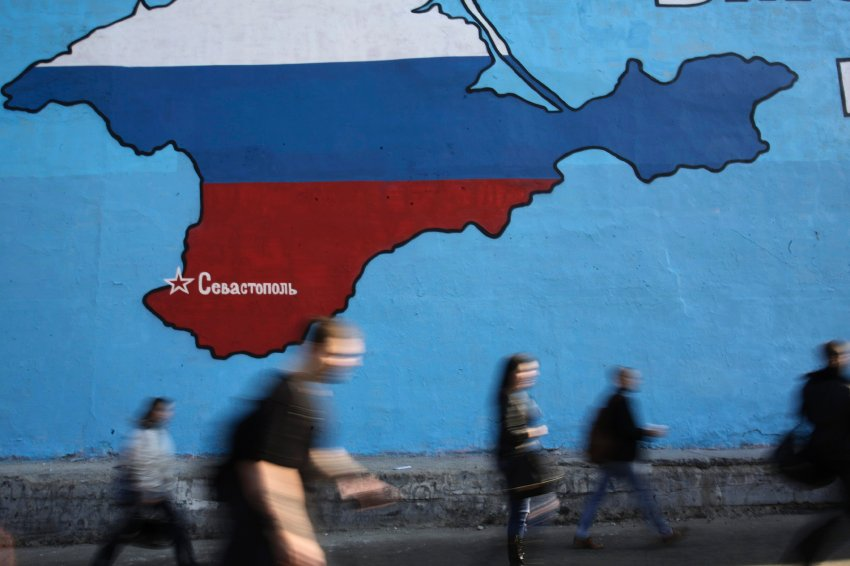 People pass a mural showing a map of Crimea in Russian national colours on a street in Moscow