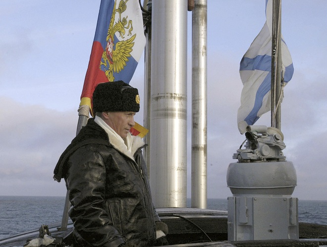 Russian President Vladimir Putin seen aboard the Arkhangelsk nuclear submarine in the Barents Sea, Russia, Tuesday, Feb. 17, 2004. At left is  presidential standard flag, at right is Russian navy flag. Putin went out to the Barents Sea on board the Arkhangelsk nuclear submarine to observe the maneuvers set to involve numerous missile launches and flights of strategic bombers in what Russian media described as the largest show of military might in more than 20 years.  (AP Photo/ITAR-TASS, Presidential Press Service)